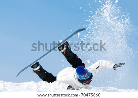 falling young man on snowboard at snowy winter - stock photo