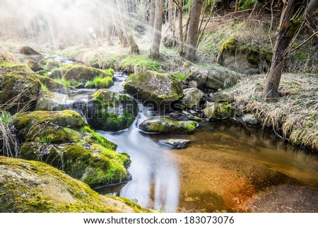 Falls on the small mountain river in a wood in spring with real light leak and sun flare