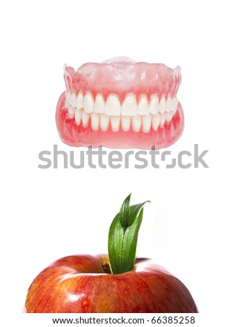 False or fake teeth with red fresh apple - healthy teeth concept -