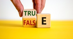 False or true symbol. Businessman flips a wooden cube and changes the word 'false' to 'true' or vice versa. Beautiful yellow table, white background, copy space. Business and false or true concept.