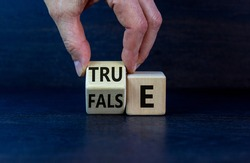 False or true symbol. Businessman flips a wooden cube and changes the word 'false' to 'true' or vice versa. Beautiful grey background, copy space. Business and false or true concept.