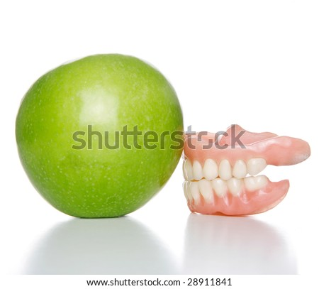 False teeth denture against green granny smith apple