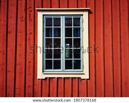 Falu red barn wall with a green and yellow window Stock fotó ©