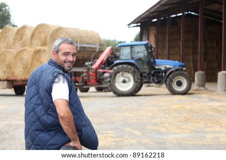 Famer stood by hay barn
