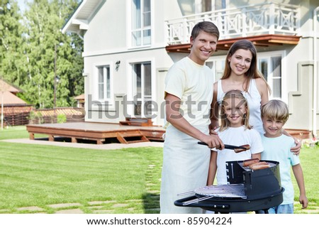 Families with children against the house with a barbecue