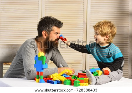 Family and childhood concept. Man with beard and boy play together on wooden wall background. Dad and kid build of plastic blocks. Father and son with happy faces create colorful robot with toy bricks #728388403