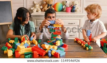 Family and childhood concept. Young family spends time in playroom. Mom, dad and boy with toys on room background build out of plastic blocks. Parents and son with busy faces make brick constructions. #1149546926