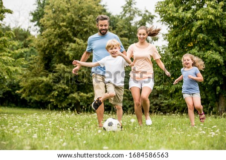 Family and children play soccer together in the garden in summer