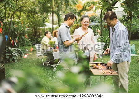 Family and Friends Gathered Together at the Table.Cooking bbq outdoor for a group of friends.Big Family Garden Party Celebration.Diverse Neighbors Drinking Party Yard Concept.