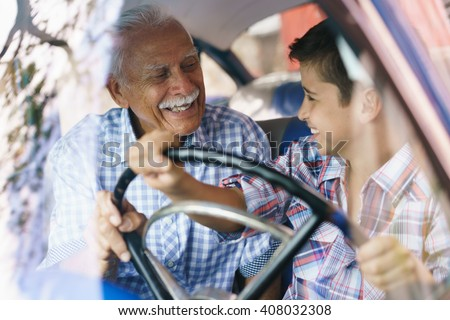 Family and Generation gap. Old grandpa spending time with his grandson and teaching him to drive. The boy holds the volante of a vintage car from the 60s. They both smile happy looking each other. #408032308