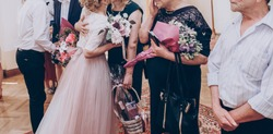 family and guests congratulating stylish wedding bride and groom with presents and flowers, celebrating love. modern couple. romantic tender moment, official wedding ceremony