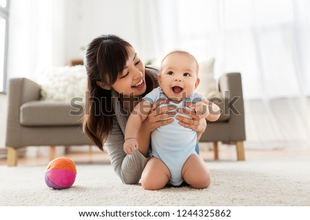 family and motherhood concept - happy smiling young asian mother with little baby at home