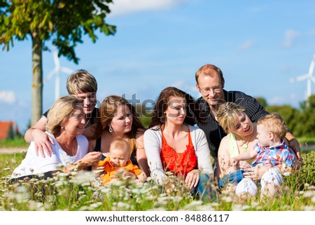 Family and multi-generation - mother, father, children and grandmother having fun on meadow in summer