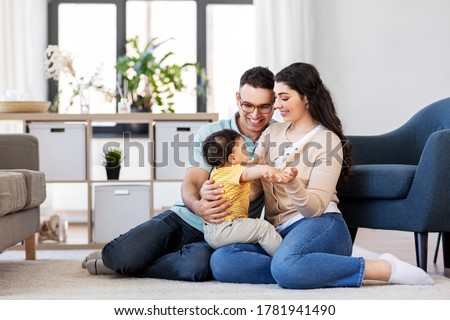 family and people concept - happy mother, father and baby son sitting on floor at home