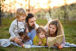 Family and small children with camera and book outdoors in spring nature, resting.
