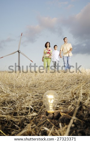 Family and wind turbines; go for a walk between wind turbine; light bulb in the ground, concept of ecology and alternative energy