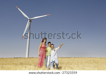 Family and wind turbines; go for a walk between wind turnines; concept of ecology and alternative energy