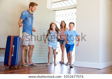 Family Arriving At Summer Vacation Rental #1052677076
