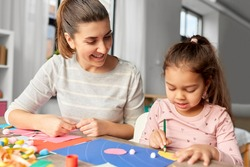 family, art and craft concept - mother spending time with her little daughter making applique of color paper at home