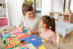 family, art and craft concept - mother spending time with her little daughter with glue making applique of color paper at home