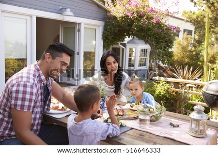 Family At Home Eating Outdoor Meal In Garden Together #516646333