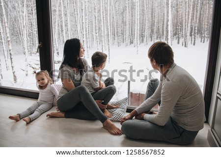 Family at home in pajamas. Daughter and son. Wake up in the morning. Hugging and kissing, looking out the window. Beautiful winter outside the window. Large windows to floor. Nice view from window.