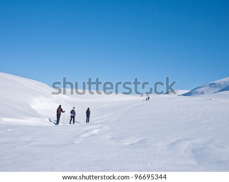 Family at ski passing a snow formation in Norwegian mountain at easter