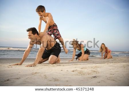 Family at the beach playing leap frog. Horizontal shot.