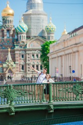 Family at the summer waterfront in Saint Petersburg. Girl outdoors with The Church of the Savior on Spilled Blood background