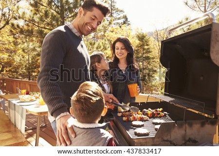 Family barbecuing on a deck in the forest #437833417