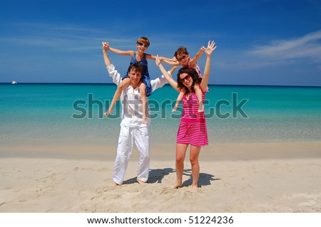 Family beach vacation. Parents with two kids having fun on the beautiful beach
