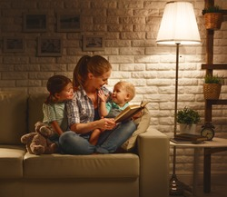 Family before going to bed mother reads children a book about a lamp in the evening