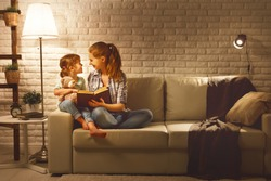 Family before going to bed mother reads to her child daughter book near a lamp in the evening