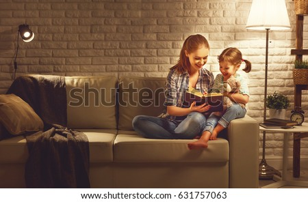 Family before going to bed mother reads to her child daughter book near a lamp in the evening\r