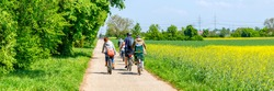 Family bike ride in Sunny spring day along fields and forest, Germany. A group of cyclists riding on the road, banner
