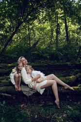 family blonde mother with two children in a white dress is lying on a tree log in the forest barefoot