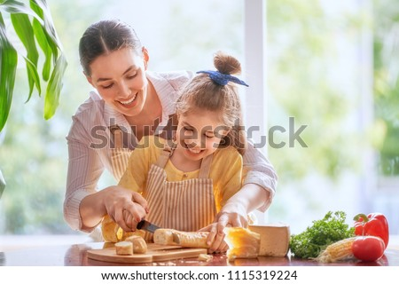 Family breakfast. Mother and her child daughter cut bread and cheese in morning.