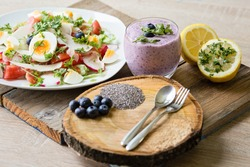 Family breakfast table with chia blueberries smoothie and fresh mixed vegetable salad