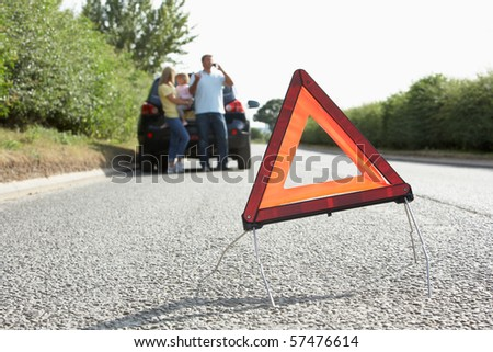 Family Broken Down On Country Road With Hazard Warning Sign In Foreground
