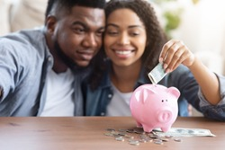 Family Budget. Happy Black Couple Putting Money Cash To Piggybank, Making Savings For Future, Sitting Together At Home