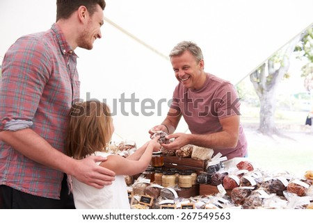 Family Buying Nuts From Stall At Farmers Market