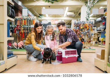 Family buying supplies for little puppy in petshop #1032806578