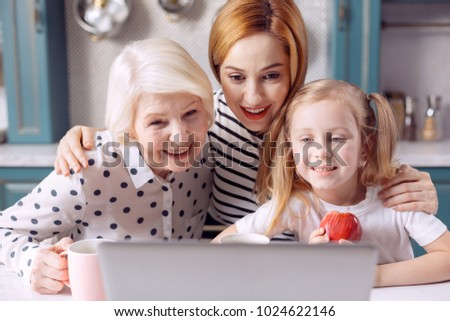 Family call. Three generations of females sitting at the kitchen counter and smiling at the web camera while having a video call with someone