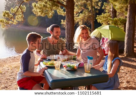 Family Camping By Lake On Hiking Adventure In Forest