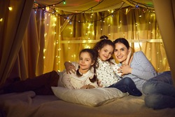 Family camping tent at home evening fun time. Happy mother and daughter children hugging sitting together looking at camera showing love and adoration emotion. Parenting and childhood concept