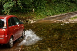 Family Car fording a river at ford an old fashioned way of crossing water without building a bridge