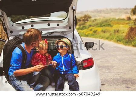 family car travel - father with two kids looking at map on road #607049249