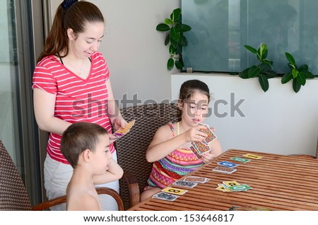 Family card game - teenage sisters and their younger brother playing a game of cards