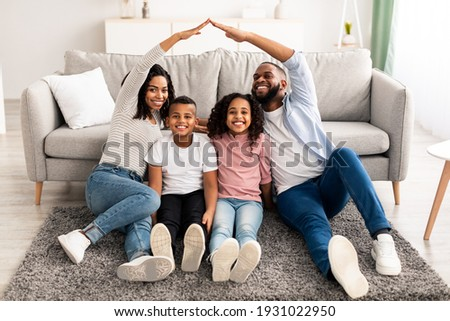 Family Care, Protection And Insurance Concept. Portrait of smiling African American parents making symbolic roof of hands above their happy children, sitting on the floor carpet in living room at home