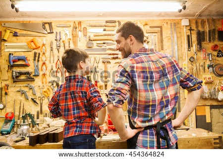 family, carpentry, woodwork and people concept - happy father and little son working with work tools and wood planks at workshop